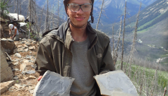 Student holding shale slabs with fossils.