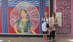 Photo of two women standing against a colourful mural