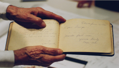 Photo of a pair of hands holding a handwritten book. The entry reads: Dear George, Words fail me. Yours truly, Kaye Uda.