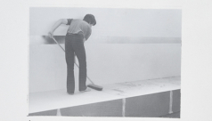 Black and white photo of a man mopping a platform