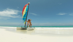 A man & a woman in bathing suits pose on a small catamaran on a sun-lit, white sand beach
