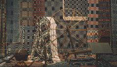 Photograph of textiles behind a spinning wheel