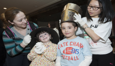 ROM Volunteer helps children try on armour during March Break 2015