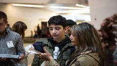 Teenage boy reads the ROM MagnusCards on a smartphone held by his mother