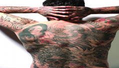 Back of man, covered with Tattoos.