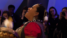 Kim Wheatley drums and sings an Anishnaabe blessing to the skeleton of the blue whale. Photo by Rachel Brown