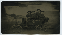 Black and white tintype photo of four men sitting on a cart in front of Niagara Falls