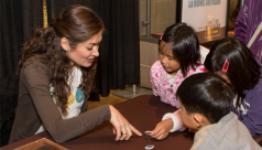 Volunteer running a hands-on activity in the gallery with children.
