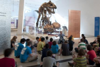 Kids sitting in front of a dinosaur at the ROM