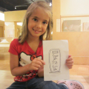 """a girl holds a paper showing the name """"Charlotte"""" in hieroglyphs"""