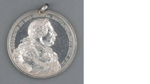 photo of a silver medal with a face in profile
