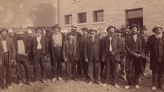 a sepia-toned photo of male prisoners standing in a line