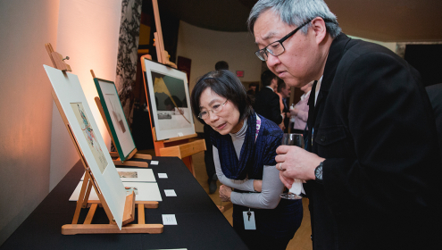 A man and a woman look intently at Japanese art