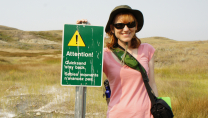 "Nicole Richards standing beside a sign reading ""Attention! Quicksand"""