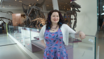 photo of Sarah in a purple dress standing in front of dinosaurs